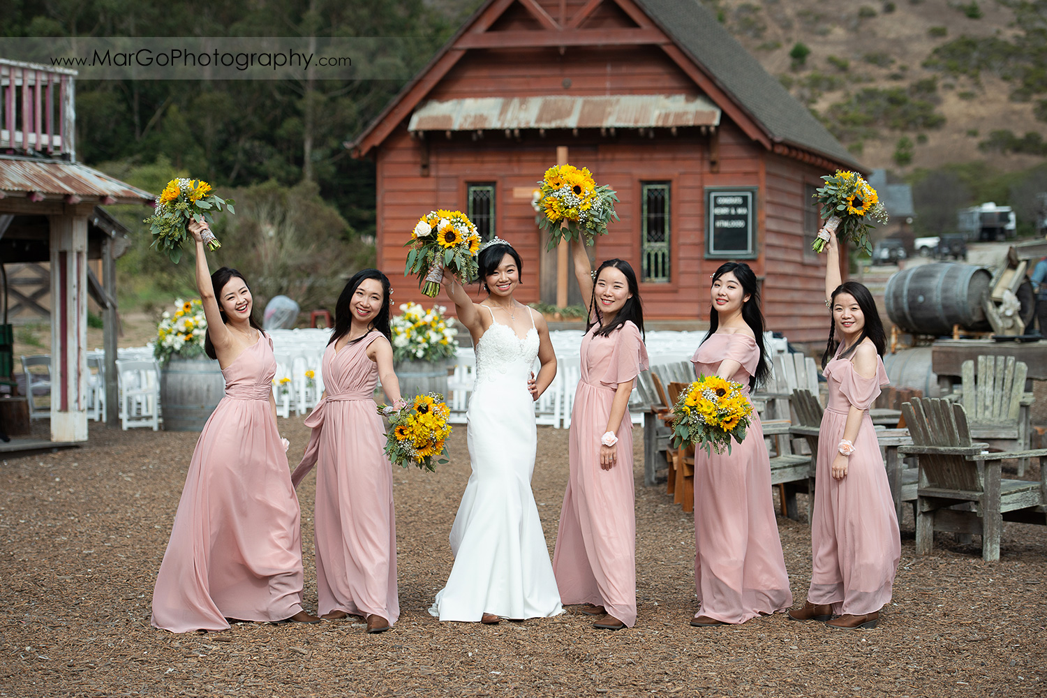 bride in white dress and bridesmaids in pink dresses showing yellow flower bouquets at Long Branch Saloon & Farms in Half Moon Bay - focus on girls