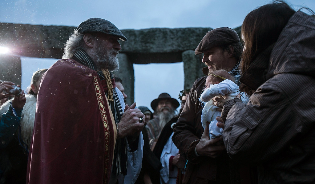 . Rollo Maughfling, Archdruid of Stonehenge & Britain, (L) blesses baby Jim, held by his father Dan Lobb and watched by mum Kirsty Lobb (R) as druids, pagans and revelers gather, hoping to see the sun rise as they take part in a winter solstice ceremony at Stonehenge on December 21, 2013 in Wiltshire, England.  (Photo by Matt Cardy/Getty Images)