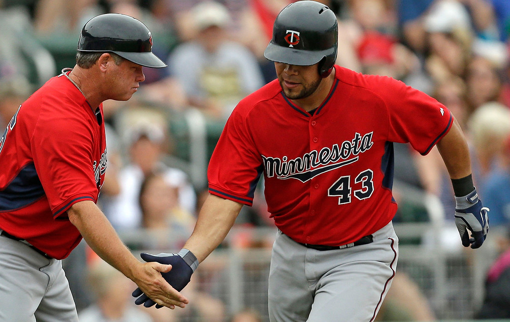 . Minnesota Twins\' Josmil Pinto (43) is greeted by third base coach Joe Vavra after hitting a home run during the seventh inning of an exhibition baseball game against the Boston Red Sox in Fort Myers, Fla., Saturday, March 29, 2014. The Twins won 7-4. (AP Photo/Gerald Herbert)