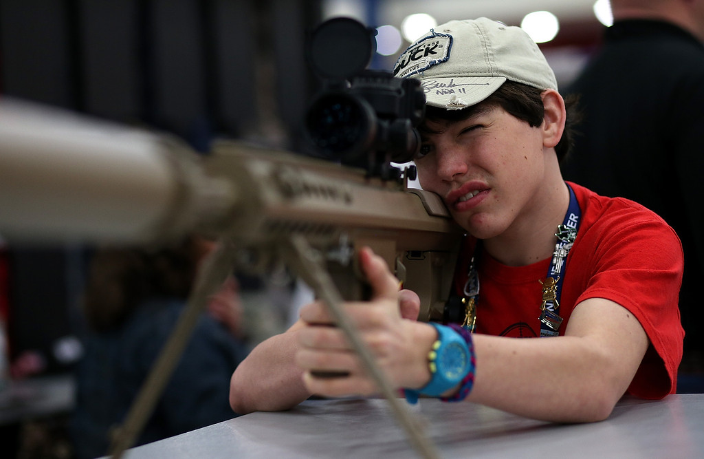 . HOUSTON, TX - MAY 04:  An young attendee inspects a high power sniper rifle during the 2013 NRA Annual Meeting and Exhibits at the George R. Brown Convention Center on May 4, 2013 in Houston, Texas.  More than 70,000 peope are expected to attend the NRA\'s 3-day annual meeting that features nearly 550 exhibitors, gun trade show and a political rally. The Show runs from May 3-5.  (Photo by Justin Sullivan/Getty Images)