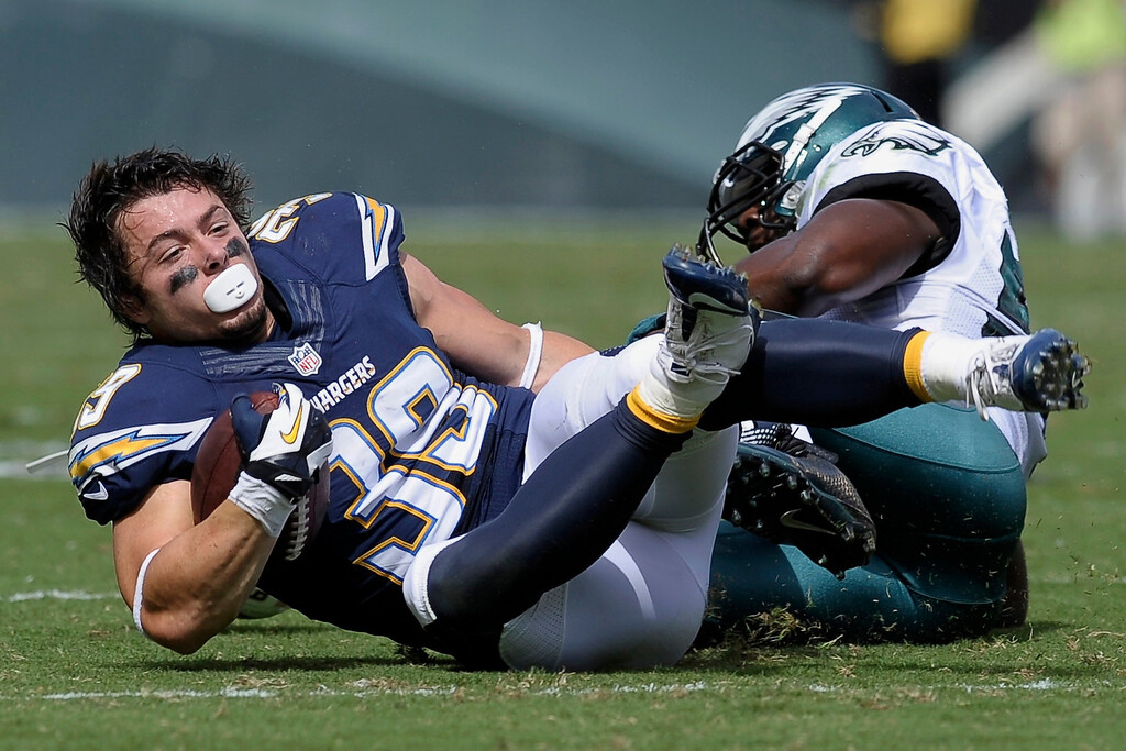 . San Diego Chargers\' Danny Woodhead, left, loses his helmet as he is tackled by Philadelphia Eagles\' DeMeco Ryans during the first half of an NFL football game on Sunday, Sept. 15, 2013, in Philadelphia. (AP Photo/Michael Perez)
