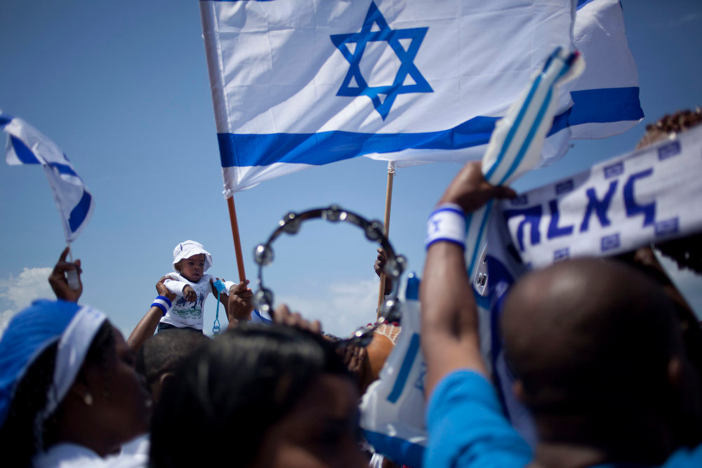 . An African migrant worker holds Israeli flags during Independence Day in Tel Aviv, Tuesday, April 16, 2013. Israel is celebrating its annual Independence Day, marking 65 years since the founding of the state in 1948. (AP Photo/Ariel Schalit)