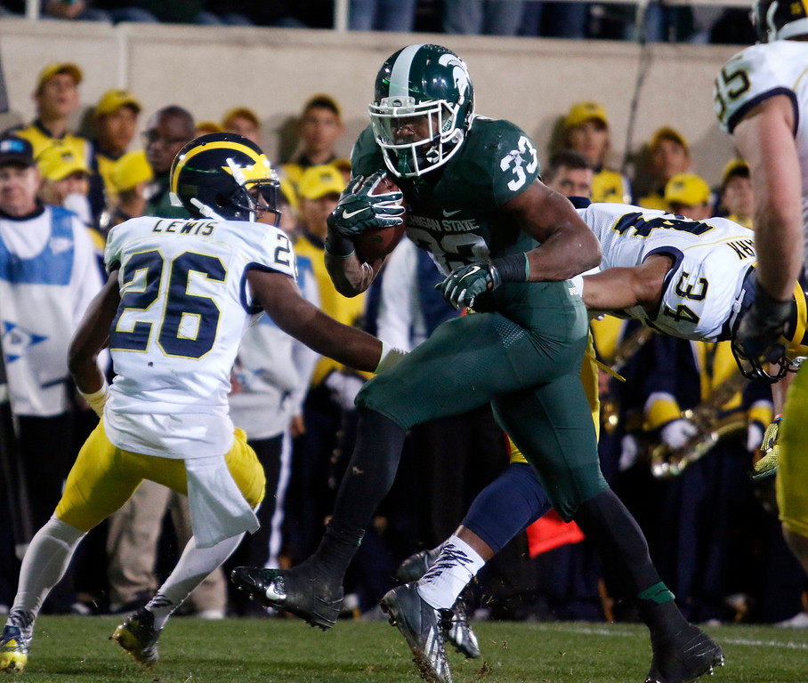 . Michigan State\'s Jeremy Langford (33) gets past Michigan\'s Jourdan Lewis (26) and Jeremy Clark (34) for a touchdown during the fourth quarter of an NCAA college football game, Saturday, Oct. 25, 2014, in East Lansing, Mich. Langford had 177 yards rushing and three touchdowns in Michigan State\'s 35-11 win. (AP Photo/Al Goldis)