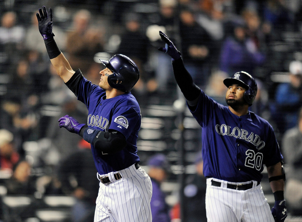 . Colorado Rockies Troy Tulowitzki, left, and Wilin Rosario, right, celebrate a home run by Tulowitzki in the sixth inning of the MLB  baseball game against the Chicago White Sox on Monday, April 7, 2014, in Denver. The Rockies won 8-1. (AP Photo/Chris Schneider)