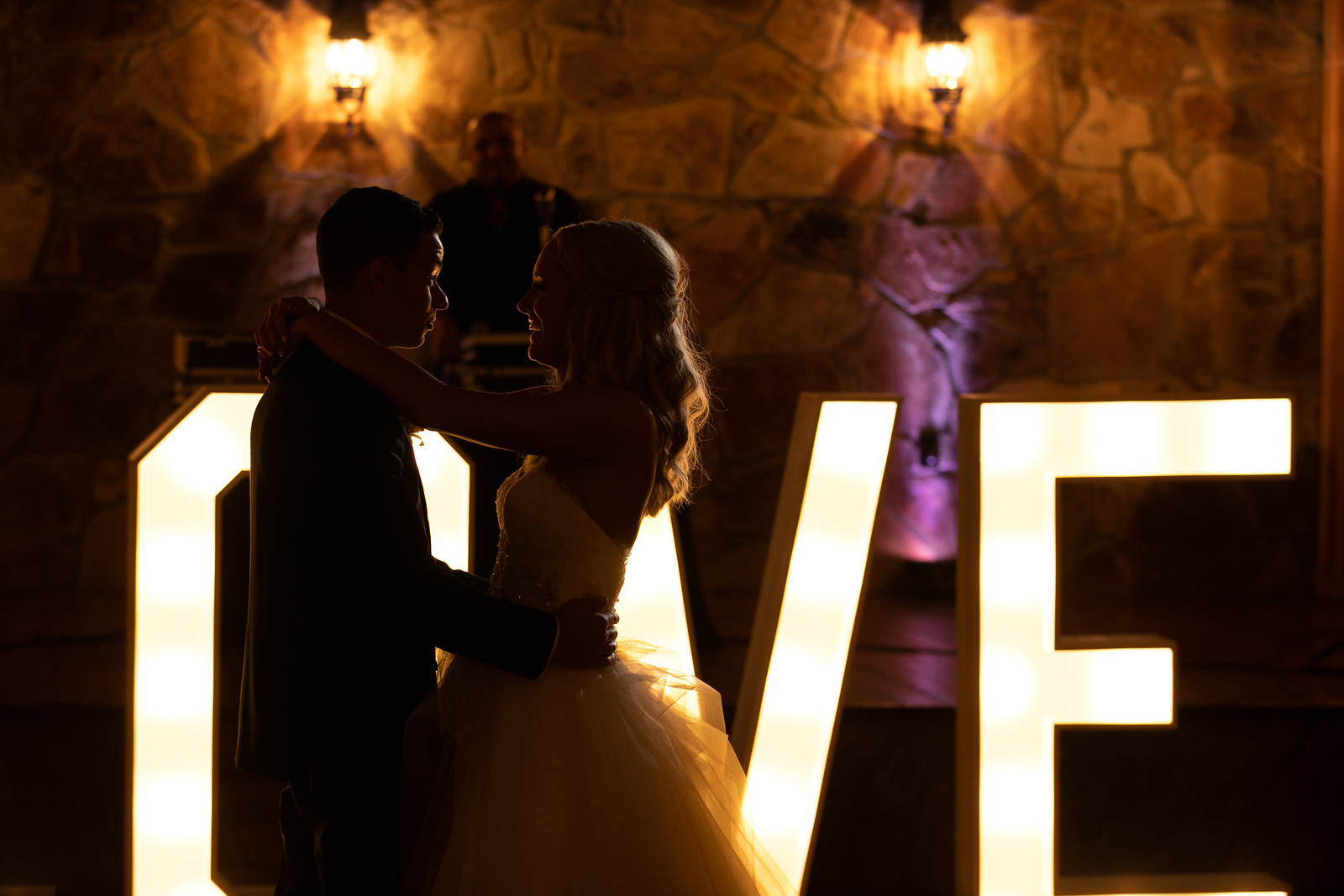 a bride and groom dancing on their wedding night in front of lit signage that says LOVE