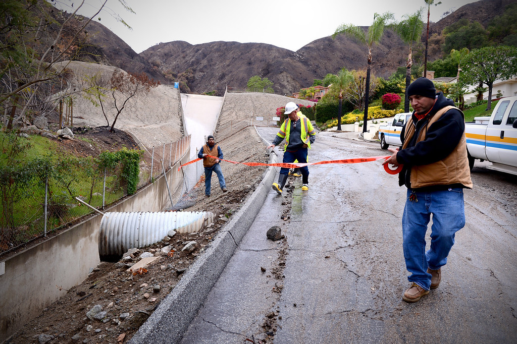 . Los Angeles Public Works places tape where a fence was knocked down by mud along the access road to the Englewild Debris Basin in Glendora Saturday, March 1, 2014.  The debris basin, one of four key debris basins in the Colby Fire burn area, is about half full and is expected to hold out through the duration of the storm. (Photo by Sarah Reingewirtz/Pasadena Star-News)
