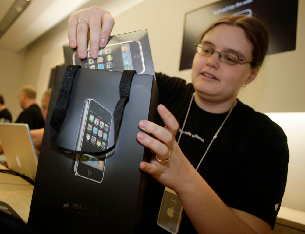 . Employee Sendra Shallow packages the first iPhone purchased at the Apple store in the Cherry Creek Mall in east Denver on Friday, June 29, 2007. Hundreds of people who lined up to be among the first to get their hands on Apple Inc.\'s coveted iPhone are now the braggarts and guinea pigs for the latest must-have, cutting-edge piece of techno-wizardry.  (AP Photo/David Zalubowski)