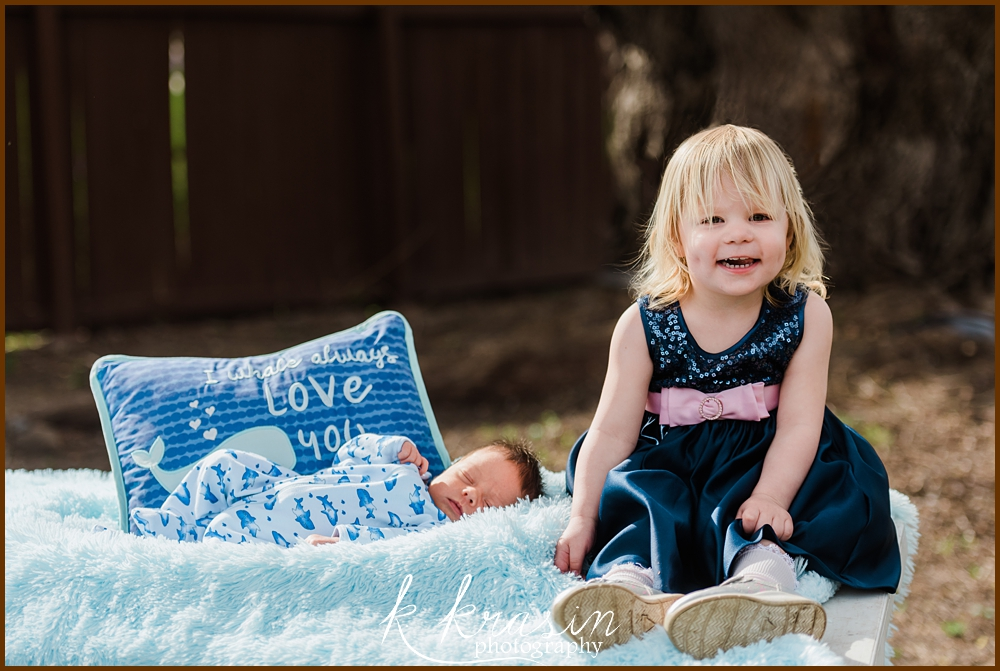 Newborn baby boy with toddler sister sitting by a pillow