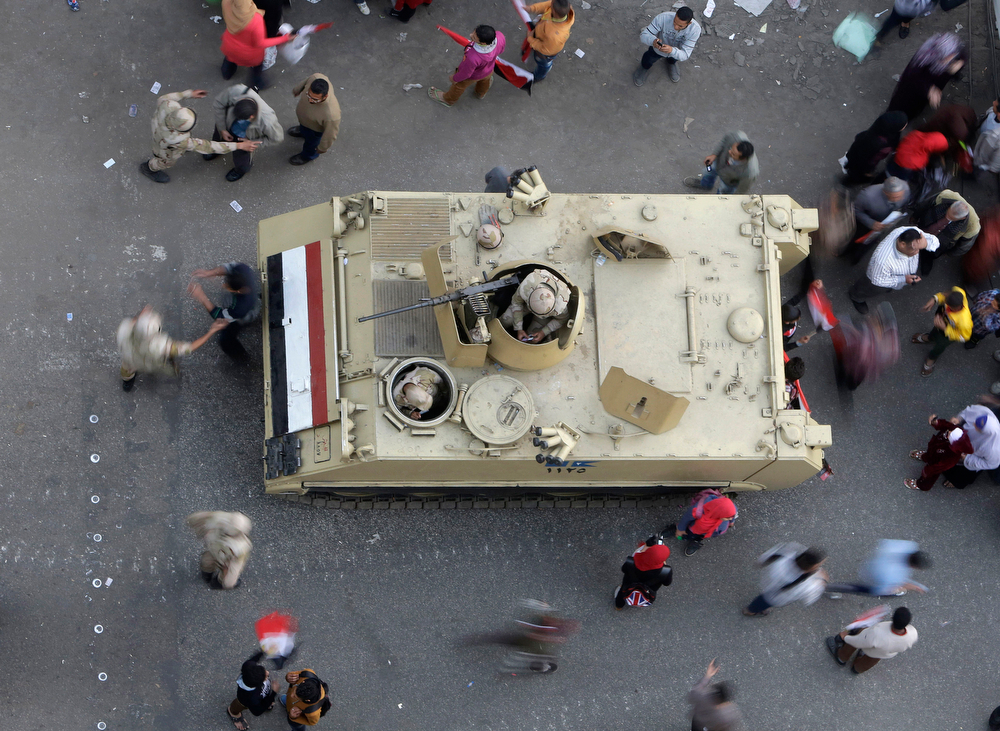. Egyptians walk around an armored personnel carrier parked at a pro-military rally marking the third anniversary of the 2011 uprising in Tahrir Square in Cairo, Egypt, Saturday, Jan. 25, 2014. Egyptian riot police have fired tear gas to disperse hundreds of supporters of ousted Islamist President Mohammed Morsi protesting as the country marks the third anniversary of the 2011 uprising, as supporters of the military gathered in rival rallies in other parts of the capital, many of them urging military chief Gen. Abdel-Fattah el-Sissi, the man who removed Morsi, to run for president. (AP Photo/Amr Nabil)