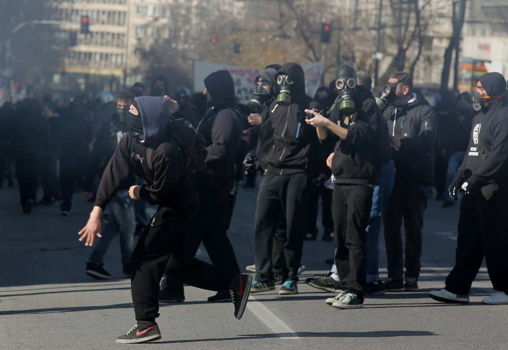 Description of . Masked protesters throw rocks at policemen following an anti-austerity march during a 24-hour strike in Athens February 20, 2013. Tens of thousands of Greeks took to the streets of Athens on Wednesday during a nationwide strike against wage cuts and high taxes that kept ferries stuck in ports, schools shut and hospitals with only emergency staff.  REUTERS/Costas Baltas/ICON