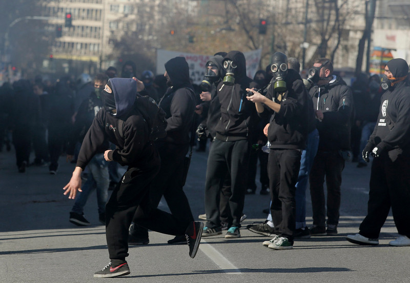 . Masked protesters throw rocks at policemen following an anti-austerity march during a 24-hour strike in Athens February 20, 2013. Tens of thousands of Greeks took to the streets of Athens on Wednesday during a nationwide strike against wage cuts and high taxes that kept ferries stuck in ports, schools shut and hospitals with only emergency staff.  REUTERS/Costas Baltas/ICON