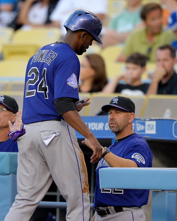 . Colorado Rockies\' Dexter Fowler, left, is congratulated by manager Walt Weiss after scoring on a sacrifice by Troy Tulowitzki during the first inning of their baseball game against the Los Angeles Dodgers, Friday, July 12, 2013, in Los Angeles.  (AP Photo/Mark J. Terrill)