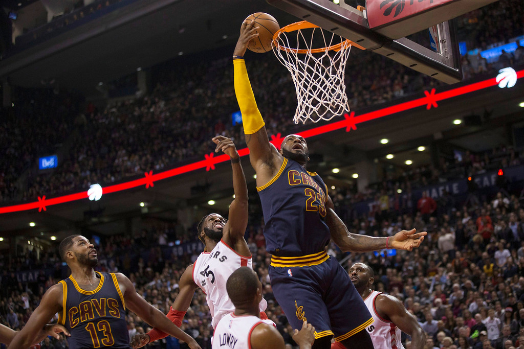 . Cleveland Cavaliers forward LeBron James scores as Toronto Raptors forward DeMarre Carroll, center left, defends during the second half of an NBA basketball game in Toronto on Friday, Oct. 28, 2016. (Chris Young/The Canadian Press via AP)