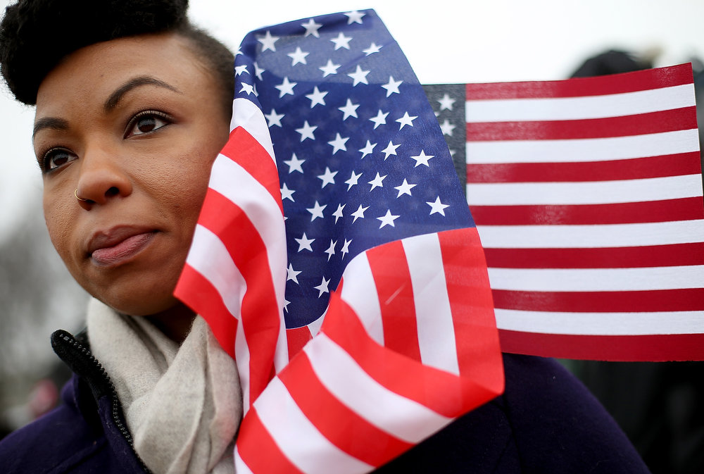 Description of . Quinnette Ellis from Tampa Bay, Florida stands with flags near the U.S. Capitol building on the National Mall after the Inauguration ceremony on January 21, 2013 in Washington, DC. U.S. President Barack Obama was ceremonially sworn in for his second term today.  (Photo by Mario Tama/Getty Images)