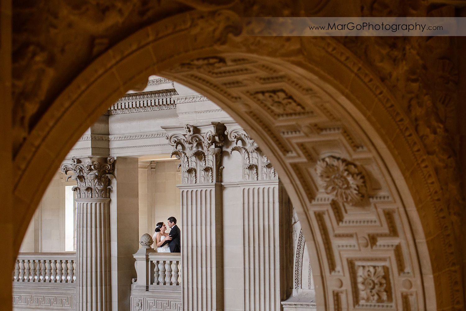 bride and groom through the arch in San Francisco City Hall
