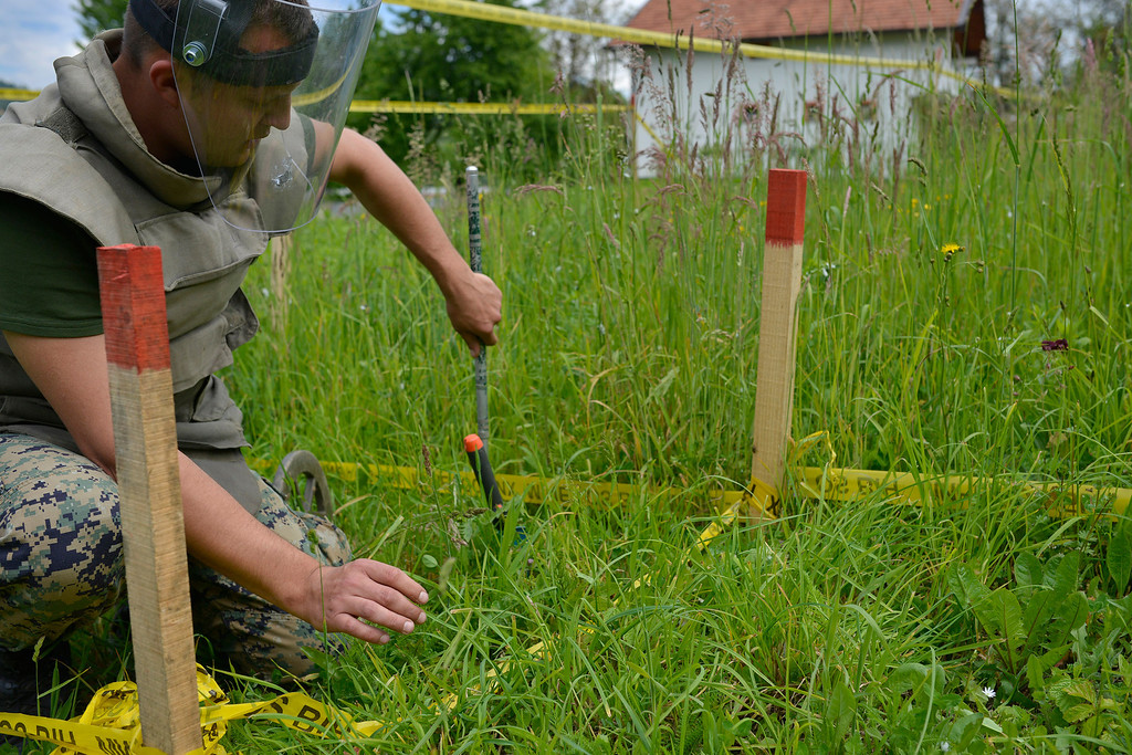 . A Bosnian soldier searches for mines in fields near the banks of the river Bosnia which were flooded, near the town of Visoko 30 km north of Sarajevo, Bosnia-Herzegovina on Tuesday May 20, 2014. At least two dozen people have died and tens of thousands of people have been forced from their homes. But in addition to the usual dangers, the flooding has unearthed landmines left over from Bosnia\'s 1992-95 war and washed away the signs that marked them. (AP Photo/Sulejman Omerbasic)