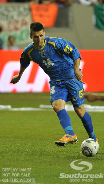 Bosnia-Herzegovina's Forward Vedad Ibisevic (#14) makes a pass in Soccer action between Bosnia-Herzegovina and Mexico.  Mexico defeated Bosnia-Herzegovina 2-0 in the game at the Georgia Dome in Atlanta, GA.