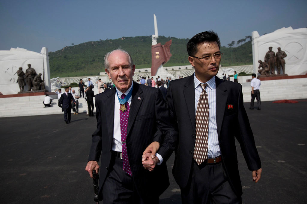 . Retired U.S. Navy captain and Korean War veteran Thomas Hudner, left, is escorted by a North Korean official as he leaves a cemetery for Korean War veterans after an opening ceremony which marks the 60th anniversary of the signing of the armistice that ended hostilities on the Korean peninsula, in Pyongyang, North Korea, Thursday, July 25, 2013. (AP Photo/David Guttenfelder)