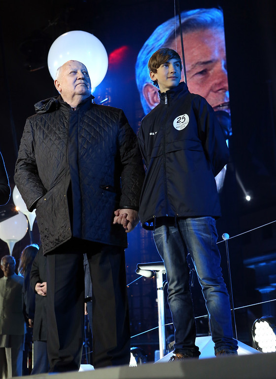 . BERLIN, GERMANY - NOVEMBER 09:  Former Soviet leader Mikhail Gorbachev (L) attends celebrations for the 25th anniversary of the fall of the Berlin Wall at the Brandenburg Gate on November 9, 2014 in Berlin, Germany. The city of Berlin is commemorating the 25th anniversary of the fall of the Berlin Wall from November 7-9 with an installation of 6,800 lamps coupled with illuminated balloons along a 15km route where the Wall once ran and divided the city into capitalist West and communist East. The fall of the Wall on November 9, 1989, was among the most powerful symbols of the revolutions that swept through the communist countries of Eastern Europe and heralded the end of the Cold War. Built by the communist authorities of East Germany in 1961, the Wall prevented East Germans from fleeing west and was equipped with guard towers and deadly traps.  (Photo by Adam Berry/Getty Images)