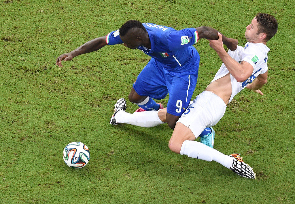 . Italy\'s forward Mario Balotelli (L) and England\'s defender Gary Cahill vie for the ball during a Group D football match between England and Italy at the Amazonia Arena in Manaus during the 2014 FIFA World Cup on June 14, 2014.  AFP PHOTO / FRANCOIS XAVIER MARIT