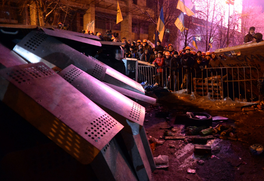 . Protesters defend their barricades in front of riot policemen on Independence Square in Kiev, on December 11, 2013. Ukrainian security forces on December 11 moved away from the Kiev city hall after a failed bid to retake the building from some 200 opposition activists who have occupied it for over a week, an AFP correspondent reported. The buses of the Berkut anti-riot police drove away from the building after failing to storm it due to the sheer number of demonstrators and after they were hosed with freezing water by activists inside.  VASILY MAXIMOV/AFP/Getty Images