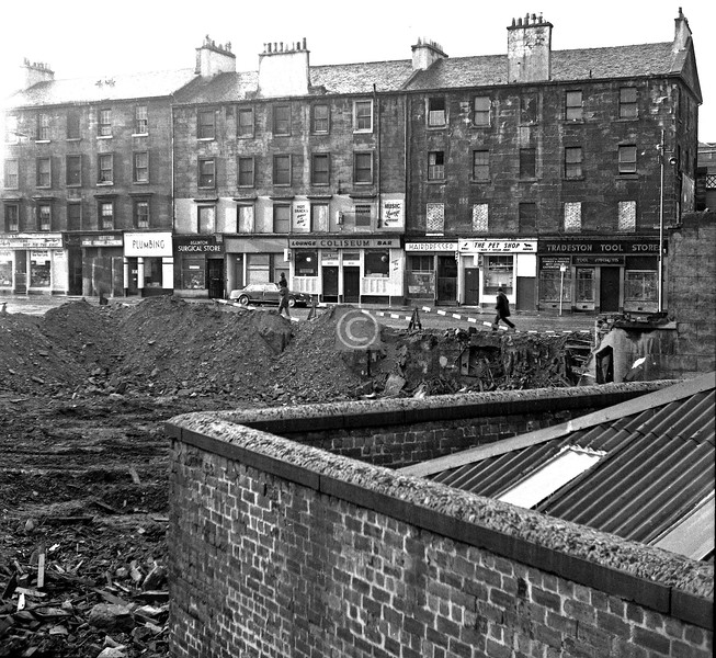 Eglinton St, west side between Cook St and Wallace St.   after some recent demolition. The Coliseum Bar was notable for a collection of photographs on display, showing stars of music-hall and cinema who had popped in for a quick one after a show or a premiere at the (late lamented) Coliseum across the road.   I suppose the roof in the foreground must have belonged to the old Bridge St subway station.    December 1973