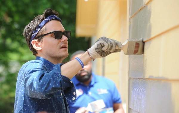 Grammy award-winning musician John Mayer paints the home of Army veteran Cliff Malone during the Veterans Build in Shreveport.