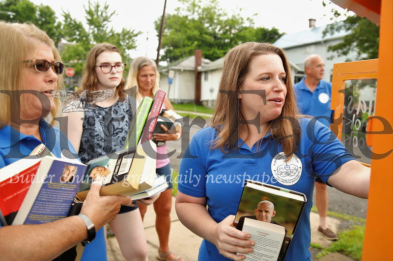 Amy Rubinosky (right) and Nancy Miller(left) load books into the new book boxes in Evans City by th EDCO Park Pool, with the help of Megan Neely and Krista Novak. Seb Foltz/Butler Eagle