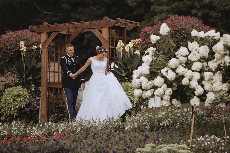 The bride leads her groom by the hand through an elaborate garden.