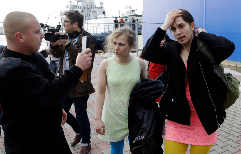 . A Russian security officer records members of the punk group Pussy Riot Nadezhda Tolokonnikova, right, and Maria Alekhina, center, after they were attacked by Cossack militia in Sochi, Russia, on Wednesday, Feb. 19, 2014. Cossack militia attacked the Pussy Riot punk group with horsewhips on Wednesday as the group tried to perform under a sign advertising the Sochi Olympics. (AP Photo/Morry Gash)