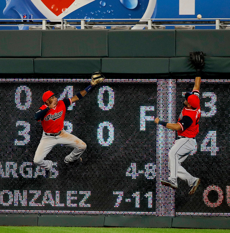. Cleveland Indians center fielder Greg Allen, left, and right fielder Melky Cabrera chase a walk-off home run by Kansas City Royals\' Hunter Dozier during a baseball game Friday, Aug. 24, 2018, in Kansas City, Mo. The Royals won 5-4. (AP Photo/Charlie Riedel)