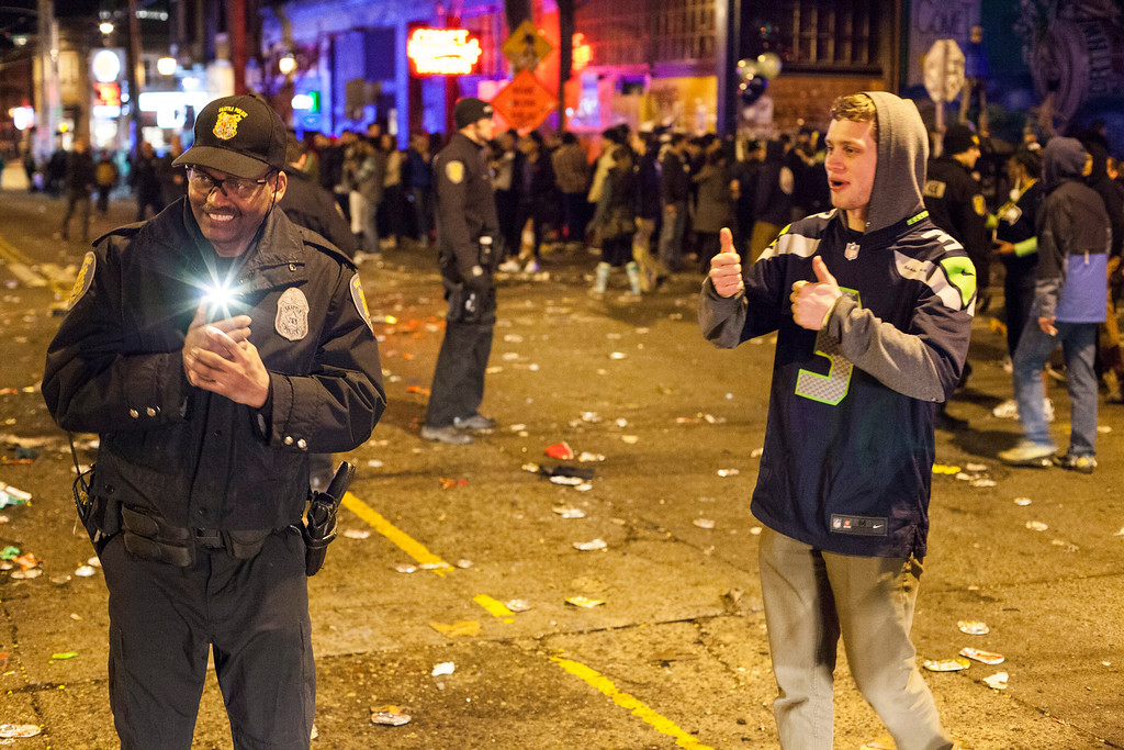 . A police officer enjoys himself while filming Seattle Seahawks fans celebrating in the street after the Seahawks won the Super Bowl on February 2, 2014 in Seattle, Washington. The Seahawks defeated the Denver Broncos 43-8 in Super Bowl XLVIII.  (Photo by David Ryder/Getty Images)