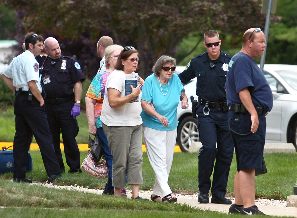 . Police evacuate people from the Sister Marie Lenahan Wellness Center on the campus of Mercy Fitzgerald Hospital after a shooting Thursday. (Times Staff / JULIA WILKINSON )