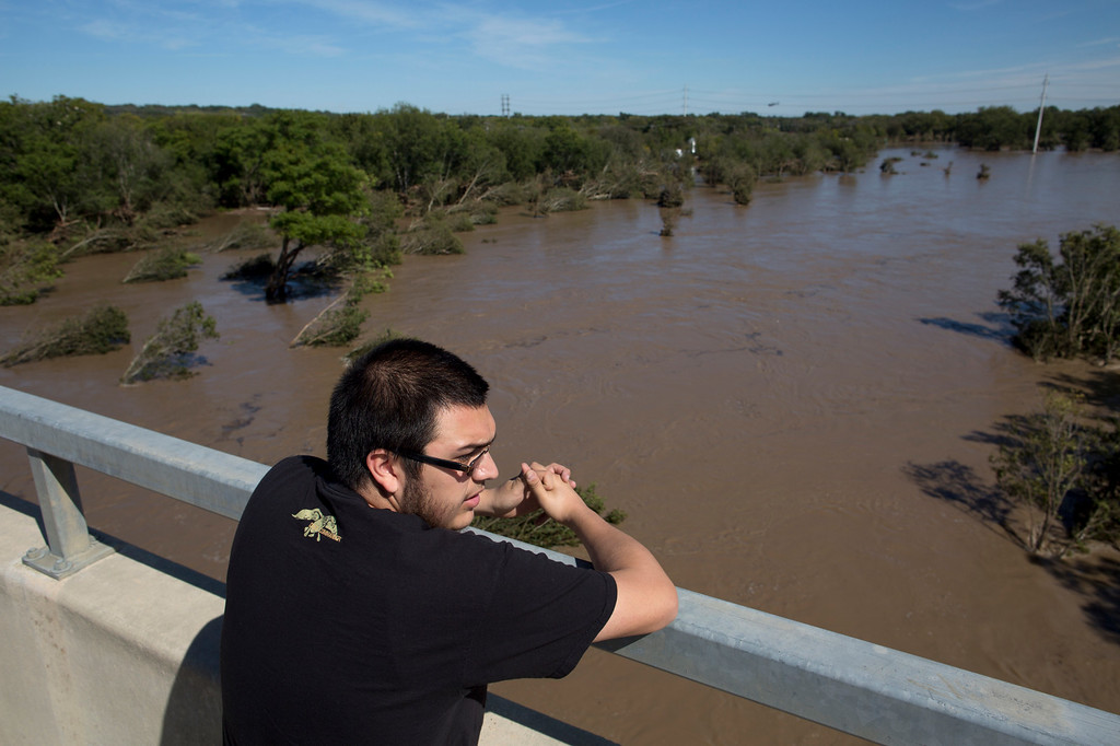 . Jake Navarro looks out over a flooded Onion Creek on Thursday Oct. 31, 2013 in Austin, Texas.  The National Weather Service said more than a foot of rain fell in Central Texas, including up to 14 inches in Wimberley, since rainstorms began Wednesday. (AP Photo/ Tamir Kalifa)