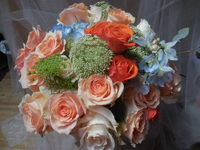 Blue hydrangea, peach , orange roses, queen anne's lace, blue delphinium $125