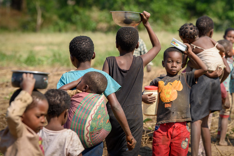 Children head home after receving  nutritional porridge during a supplemental feeding at the Child Friendly Space that Marie Ngalula, 14, and her siblings attend. Many carry some of their food home to share with others.  Marie lives with her father, Alexandre Tshimanga, her mother, Ntumba Kalombo Antoinette and her brothers and sisters: 1-Kena Tshimanga, 12 2-Kankonde Moise, 10 3-Munamba Angel, 8 4-Musungayi Andre, 6 5-Mubuyi Tshimanga, 4  Marie lives in a small village outside of Kananga, Democratic Republic of Congo, DRC, called Tubuluku, which means antelopes (plural). Her house is a two-room hut with a thatched roof.  Handful of wooden chairs are the only furniture. She lives here with an extended family of 13.  Home Life Marie is a bright girl but there is a sadness in her eyes. Marie's mother is in the nearby health clinic with a staph infection that has caused a huge abscess on her right side. It has become very serious. As a result, Marie has assumed many of the household duties.  She's forced, at 14, to assume the duties of an adult. Besides cooking for her brothers and sisters, she sweeps up the husks from palm nuts she crushes. She saves the husks to use as kindling for the fire. Marie and her siblings all sleep together in one room, huddled together for warmth and cover by an old and torn mosquito net.  Hunger Marie's family is desperately hungry in the days we visit them. Because her mother is sick and his father spends his days tending to her in the clinic, there is no money for food. Because there isn't any cassava flour and cornmeal to make fufu, a bread-like dish that's a Congolese staple, Marie and her siblings pick potato leaves from the garden. Marie sharpens a knife on a rock and uses it to chop the leaves into small pieces. She holds a bunch tightly in her left hand and runs the knife through them.  Her cousin, also named Marie Ngalula, pulls some wood from a pile and arranges it between three rocks that will hold the pot. She yanks some thatch