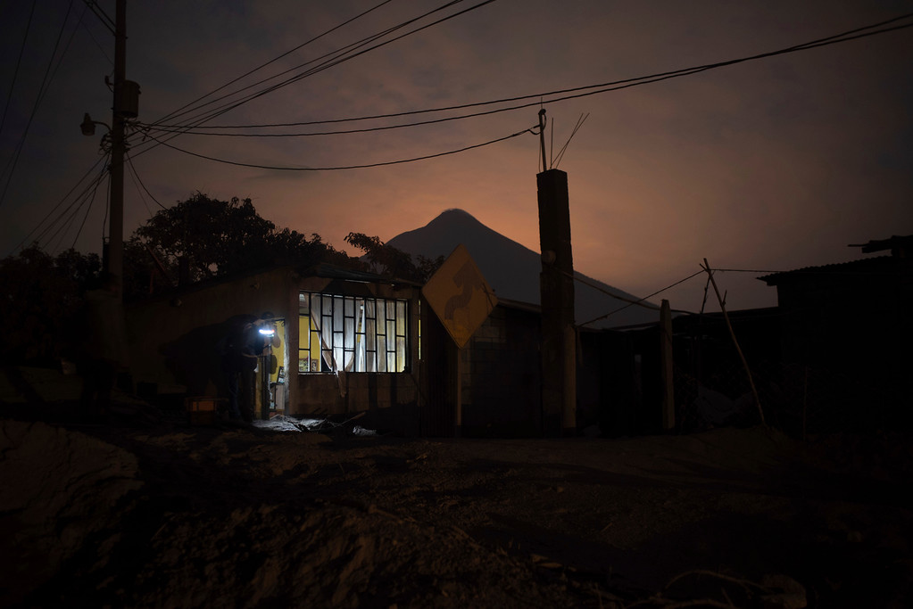 ". A journalist stands in the doorway of a home, evacuated by its inhabitants near the Volcan de Fuego, or ""Volcano of Fire,\"" in Escuintla, Guatemala, early Monday, June 4, 2018. A fiery volcanic eruption in south-central Guatemala sent lava flowing into rural communities. Rescuers struggled to reach people where homes and roads were charred and blanketed with ash. (AP Photo/Santiago Billy)"