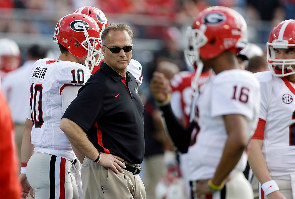 Description of . Georgia head coach Mark Richt, center, watches his team warm up prior to the Capital One Bowl NCAA football game against Nebraska, Tuesday, Jan. 1, 2013, in Orlando, Fla. (AP Photo/John Raoux)