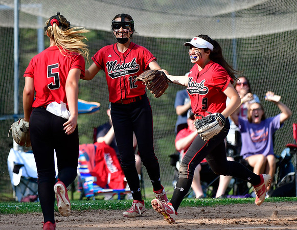 5/31/2019 Mike Orazzi | Staff Masuk's Samantha Schiebe (5), Emily Lange (12) and Kaitlyn Welch (12) celebrate a win over Bristol Eastern in the Class L Quarterfinals softball game on Friday in Monroe.