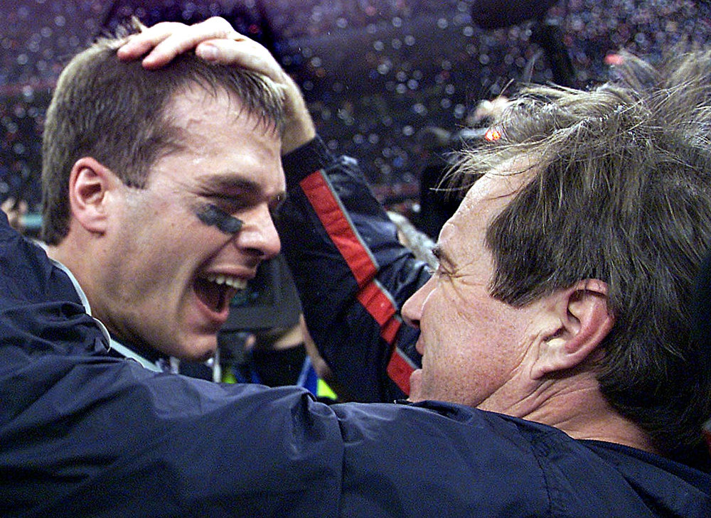Description of . New England Patriots\' quarterback Tom Brady celebrates with head coach Bill Belichick (R) after their win over the St. Louis Rams 03 February, 2002 in Super Bowl XXXVI in New Orleans, Louisiana. The Patriots defeated the Rams 20-17 for the NFL championship. JEFF HAYNES/AFP/Getty Images