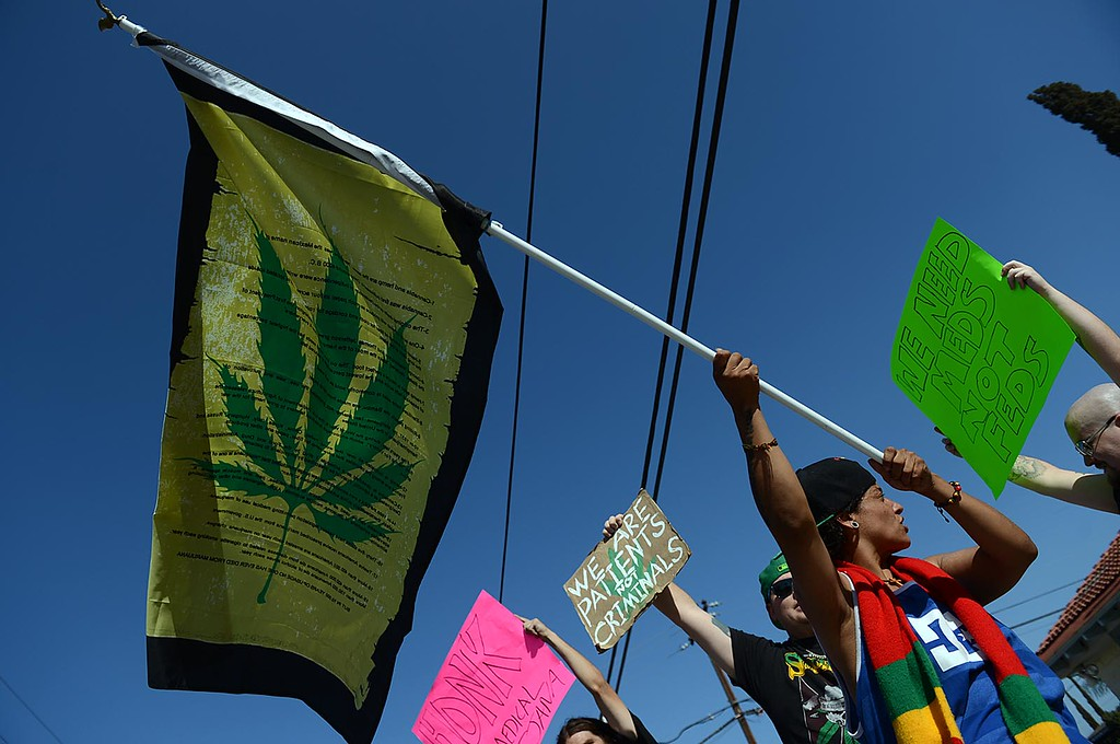 . Maria Rodriguez, 35, of Yucaipa, along with other supporters of Doc Holliday\'s Collective, in Mentone, protest the closure of the medical marijuana dispensary Monday August 12, 2013.  (Photo by Rick Sforza/Redlands Daily Facts)