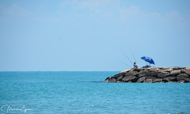Over on the east coast of Italy, near Venice, a lone fisherman on the Adriatic sea.