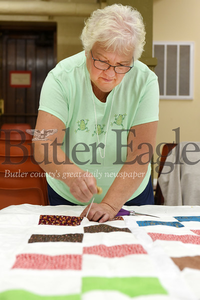 Harold Aughton/Butler Eagle: Charlotte Bupp of Meridian knots together three layers of the quilt before it is sewn together.
