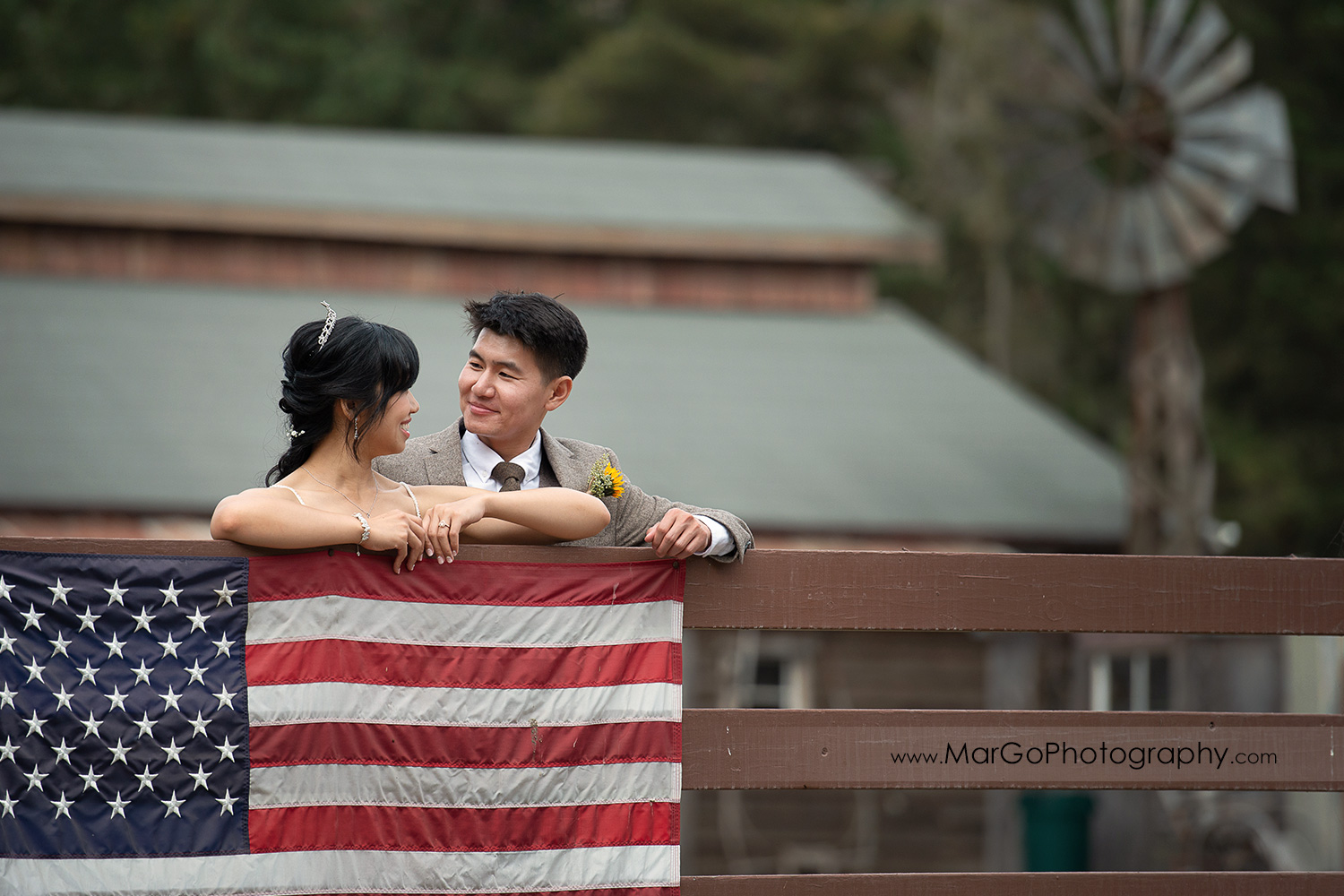 bride and groom looking at each other behind the fence with American flag at Long Branch Saloon & Farms in Half Moon Bay