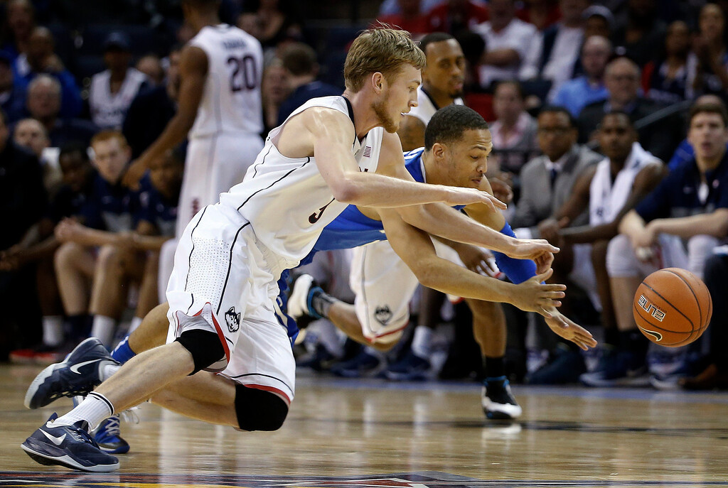 . Connecticut guard Nielss Giffey, front, and Memphis guard Michael Dixon Jr. dive for a loose ball during the second half of an NCAA college basketball game in the quarterfinals of the American Athletic Conference men\'s tournament Thursday, March 13, 2014, in Memphis, Tenn. (AP Photo/Mark Humphrey)