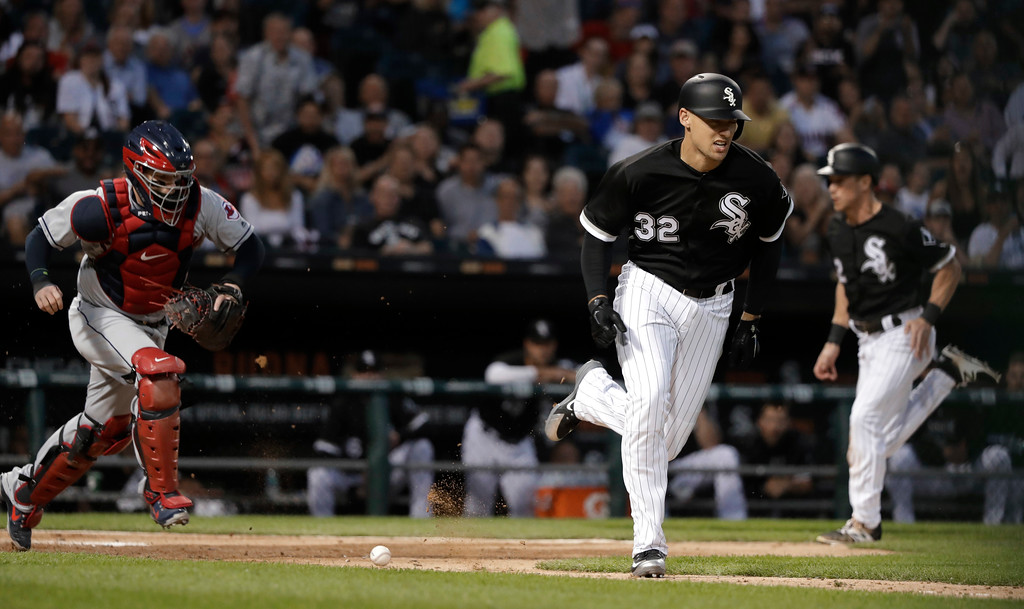 . Chicago White Sox\'s Trayce Thompson (32) heads to first on a sacrifice bunt as Charlie Tilson, right, scores from third, while Cleveland Indians catcher Roberto Perez chases the ball during the fifth inning of a baseball game Wednesday, June 13, 2018, in Chicago. (AP Photo/Charles Rex Arbogast)