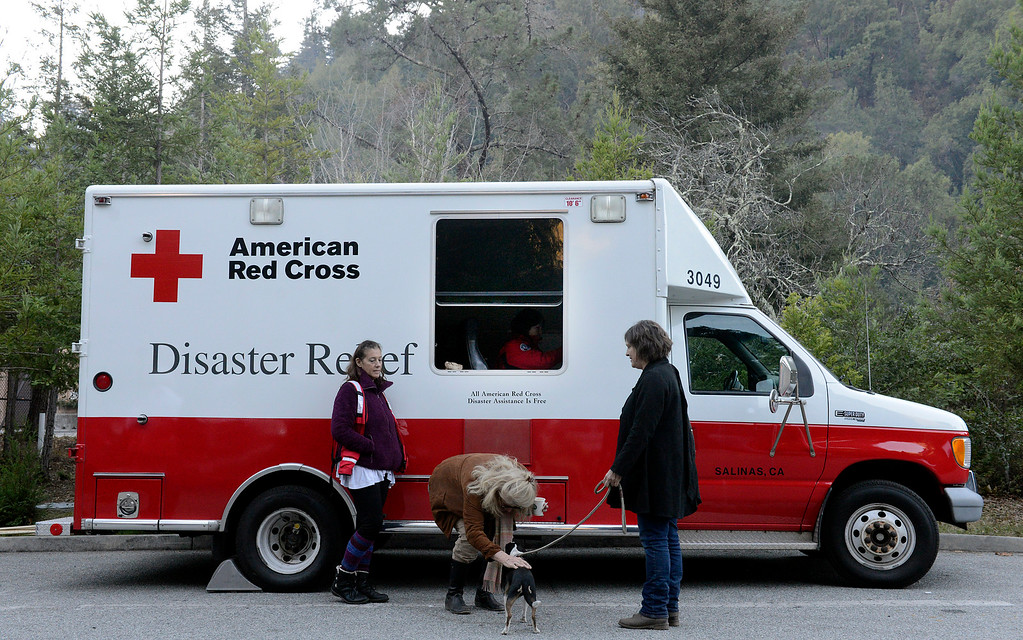 . Heidi McGurrin, greets Diane Franich\'s dog Felina as Red Cross mental health volunteer Cassandra Dobrin, left, and Americorps member Leticia Contreras, in truck, share coffee during the community meeting update on the Pfeiffer Ridge Fire in Big Sur, Calif. on Friday December 20, 2013. McGurrin is a former Big Sur resident supporting friends, Franich has a friend who fled the fire staying her house in Carmel. (Photo David Royal/ Monterey County Herald)