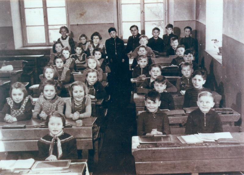 klassenzimmer im unteren alten schulhaus mit lehrer bernhard schmitt geburtsjahrgang 1946 an der einschulung 1952.jpg