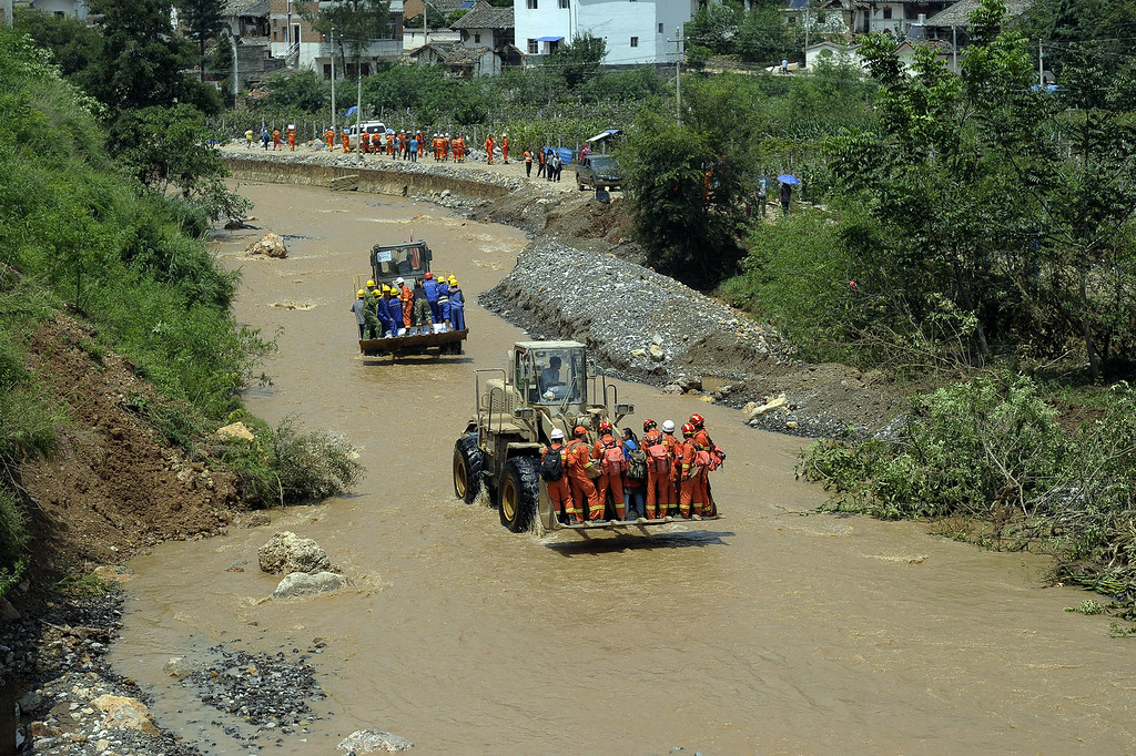 . Rescuers make their way through a river with excavators in Longtoushan township of Ludian county in Zhaotong, southwest China\'s Yunnan province on August 5, 2014. AFP PHOTO STR/AFP/Getty Images