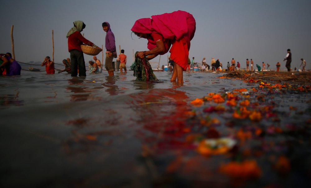 Description of . A woman washes her clothes as others participate in the Maha Kumbh festival in Allahabad, India, Tuesday, Jan. 29, 2013. Millions of Hindu pilgrims are expected to attend the Maha Kumbh festival, which is one of the world's largest religious gatherings that lasts 55 days and falls every 12 years. During the festival pilgrims bathe in the holy Ganges River in a ritual they believe can wash away their sins. (AP Photo/Saurabh Das)